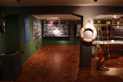 Koło ratunkowe wiszące na ścianie sali wystawowej. W tle widać banery o tematyce żeglarskiej.
