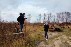 Dwoje ludzi fotografuje zardzewiałe, metalowe części, które leżą wśród wysokiej trawy.