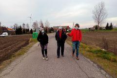 Troje dorosłych ludzi idzie drogą Jeden z mężczyzn trzyma w ręce mikrofon.