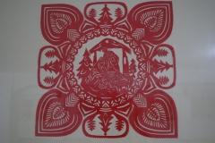 Czerwona wycinanka przedstawiajaca Świętą Rodzinę.