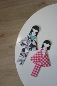 Na fotografii dwie papierowe lalki w kimonach, jedna w czarno-białym w geometryczny wzór, druga w czerwono-białą kratę. Wygląd lalek nawiązujący do kultury Japonii.