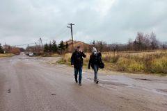 Dwoje dorosłych ludzi idzie drogą. W tle widać zabudowania i  auta. Na drodze stoją kałuże.