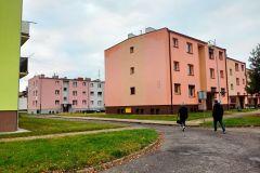 Dwoje dorosłych ludzi idzie drogą  obok dwupiętrowych budynków mieszkalnych.