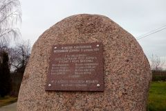 Duży kamień, do którego przytwierdzona jest tablica pamiątkowa.