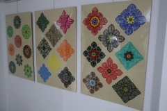 W trzech antyramach wiszących na ścianie znajdują się kolorowe wycinanki.