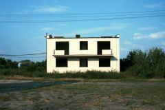 Pośród zielonych traw i krzewów stoi biały, piętrowy dom. Budynek ten stoi w stanie surowym.